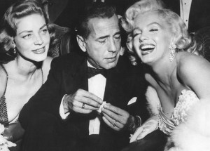 Humphrey Bogart (in tuxedo) flanked by Lauren Bacall and Marilyn Monroe.