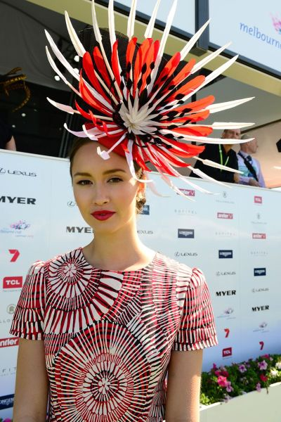 """A featherless being sporting a large """"fascinator"""" with feathers."""