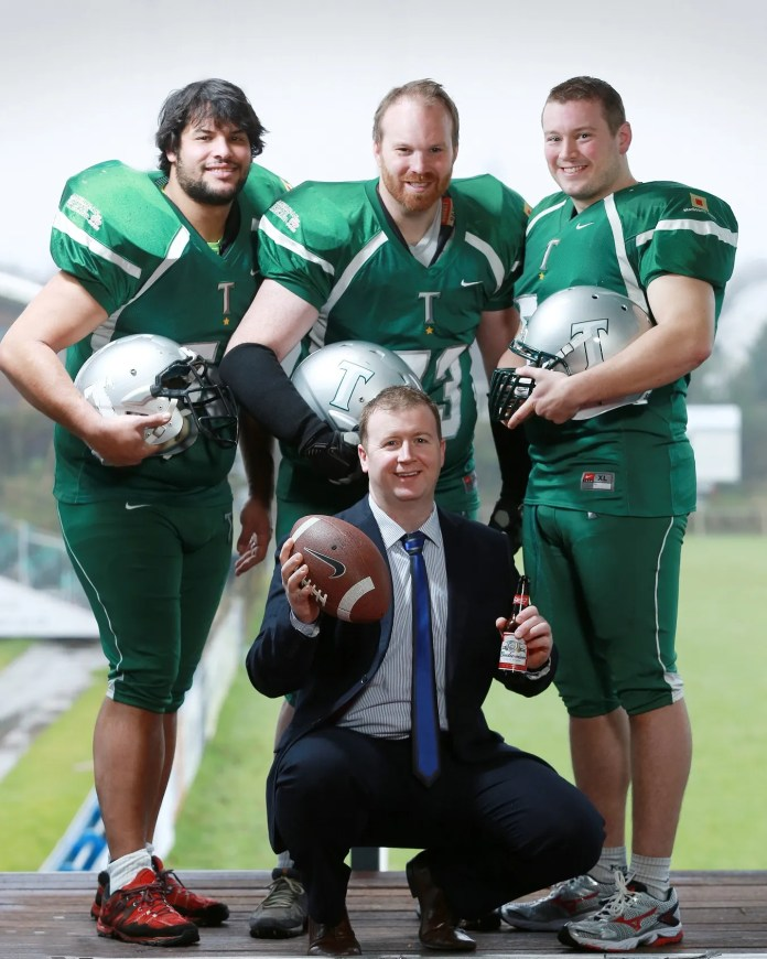 Budweiser representative Rod McCrory (front) from Tennent's NI, with Belfast Trojan players (from left) Christophe Perret , Chariman Barry Kiel, and Mark McGrath, at the team's new home grounds at Belfast Harlequins Sports Arena.