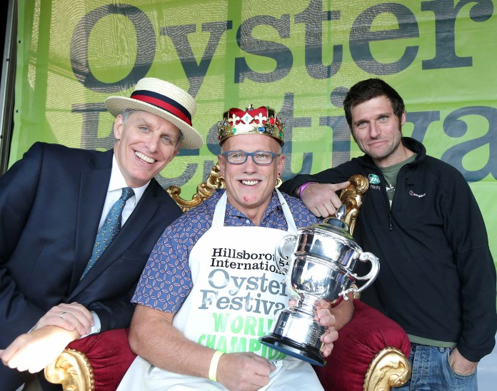 5 September 15 -   Picture by Darren Kidd / Press Eye. Pictured celebrating with the still undefeated World Oyster Eating Championship Colin Shirlow (centre) are compere George Shea (left) who flew in from New York for the competition and motor racing legend Guy Martin who was a guest judge at the TrustFord Soapbox Derby. Both of these superb events took place at the 23rd annual Hillsborough International Oyster Festival. Colin Tops The Table Again: They came, they swallowed but as always they failed to conquer. Today saw the World Oyster Eating Championship as part of the 23rd Hillsborough International Oyster Festival. This years event included a special challenge from a diminutive professional eater, Michelle Lesco, who flew all the way from Arizona  to take on Oyster King Colin Shirlow and together guzzle hundreds of oysters.  However as always, local champ Colin Shirlow ran away with the contest. Taking part in his 11th year, the Dromore man managed to put away a ÔshuckingÕ  235 oysters in just three minutes - breaking his own World Record of eating 233 oysters in 3 minutes, which he set in 2005. Colin was jubilant when he collected his crown saying, ÒIt's astonishing that I've won the championship yet again and I am delighted to have beaten my record! He went on, ÒEven if I didn't win I would still take part in the contest. The Hillsborough Oyster Festival is a fantastic event. It's so much fun and shows some of the best hospitality that Hillsborough has to offer.Ó It's hardly surprising the former boxer managed to beat the other contenders to the title Ð he's done exactly the same thing every single one of the 11 years he's taken part in the competition and this win was on the 10th anniversary of his World Record, which until now he had only managed to equal in 2013. As ever Colin puts his unusual technique down to the training he received during his boxing days. ÒIt's about speed and rhythm,Ó he explained. ÒYou can't get either until you focus but once you find the right rhythm then you just keep going.Ó Others in the world of professional eating agree and many study Colin's techniques from YouTube videos of the champ including the defeated Michelle Lesco. ÒOf course I wanted to win,Ó admitted the 31 year-old teacher from Tucson. ÒBut this game is also about the taking part. Watching Colin go is like watching a machine!,Ó she said. The Hillsborough Oyster Festival concludes this Sunday, September 6th with the Supercar Sunday Event where supercar fanatics can take their dream ride for a spin or even go on an excursion. For more information to go www.hillsboroughoysterfestival.com. Ends. For further information please contact Julie McCabe (07801 989950), Brittany Breslin or Jessica Fok at Massive PR on 028 9024 0250 or email Julie@massivepr.tv / Brittany@massivepr.tv / Jessica@massivepr.tv.