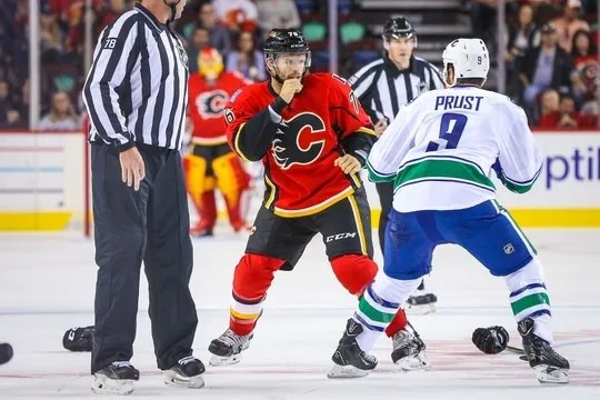 Sep 25, 2015; Calgary, Alberta, CAN; Calgary Flames right wing Blair Riley (76) and Vancouver Canucks right wing Brandon Prust (9) fight during the first period at Scotiabank Saddledome. Mandatory Credit: Sergei Belski-USA TODAY Sports