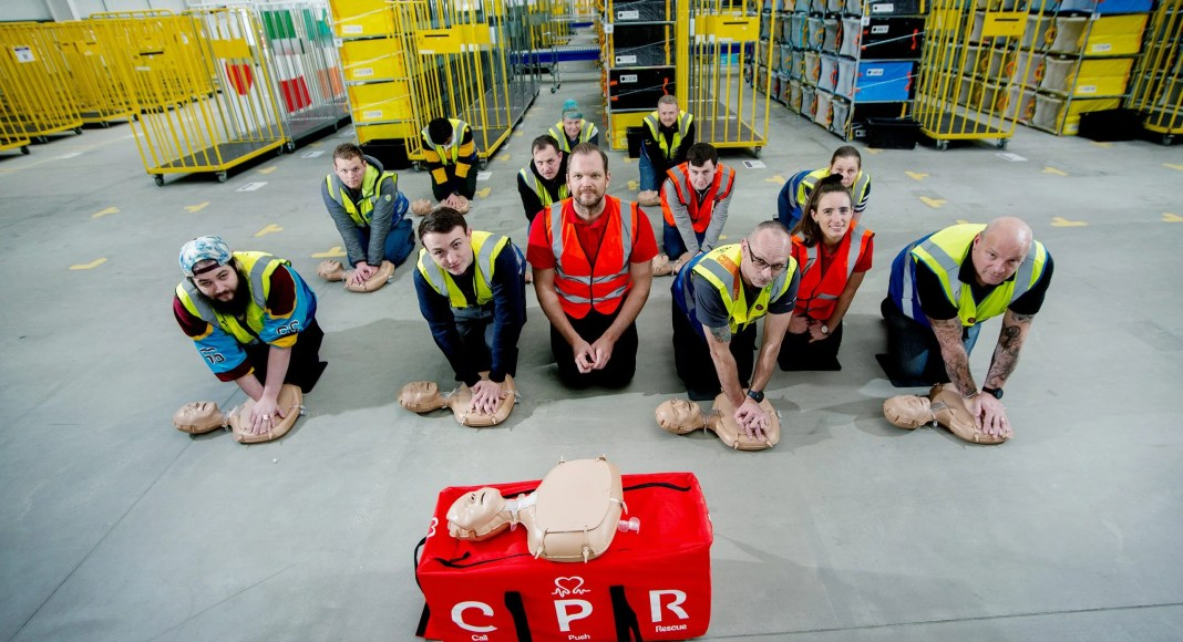 BHF trainers Gareth and Helen, at front with orange vests, teaching Amazon workers how to become CPR trainers