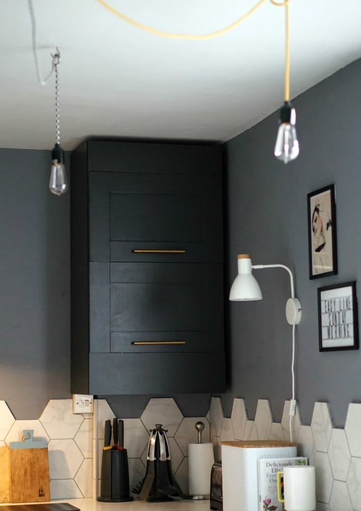 A boxed in boiler in a dark grey kitchen with yellow industrial lights