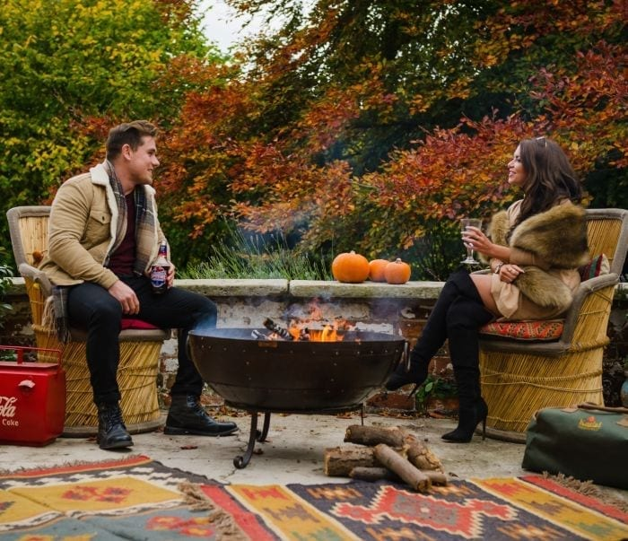 Two people sat outside round a fire bowl