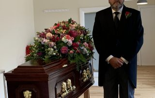 Funeral Director Chris Foster standing next to coffin