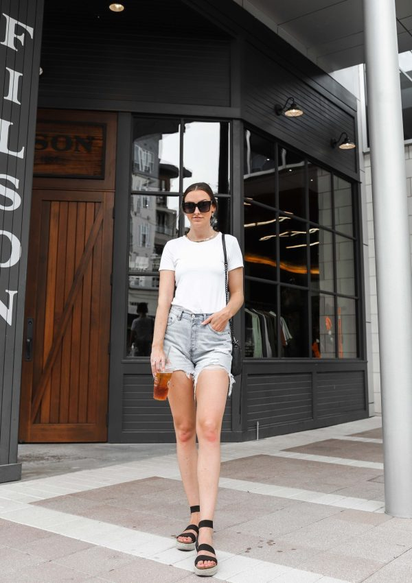 woman in white tshirt denim cutoff shorts and sandals