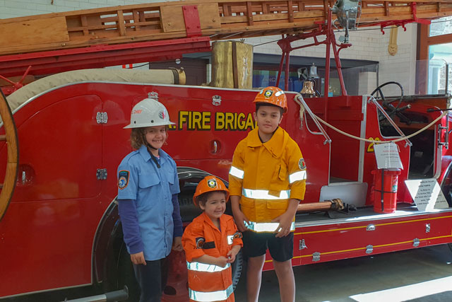 kids dressed up as fire fighters in front of an old fashioned fire truck