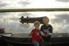 The boys loved to explore and walk around town. Here they are climbing on boats near the river.