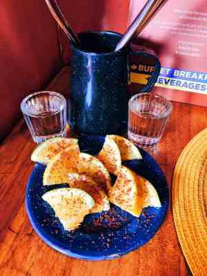 Mezcal tasting with two shot glasses and chili covered lemons