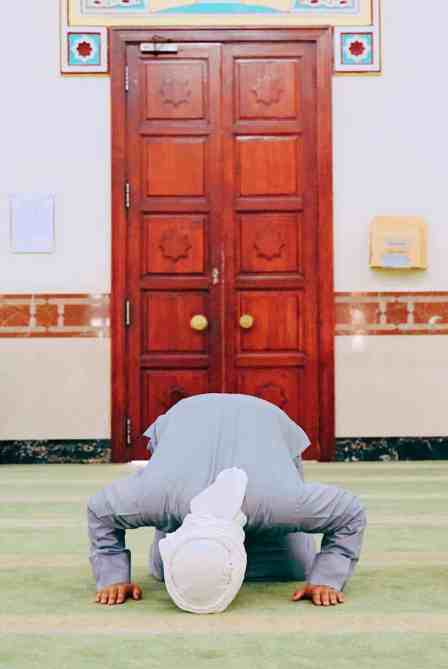Muslim man teaching how to pray at Jumeirah Mosque, one of the top things to do in Dubai.