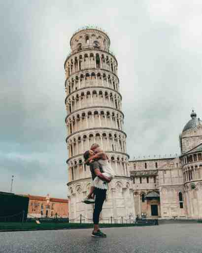 Man holding woman in beige dress embracing in front of the leaning tower of Pisa.
