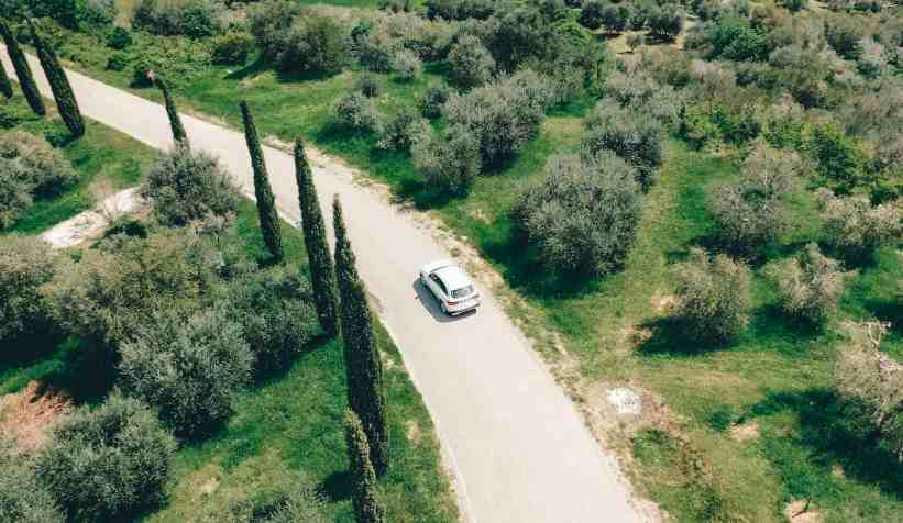 Aerial view of a car driving through the windy roads of Tuscany