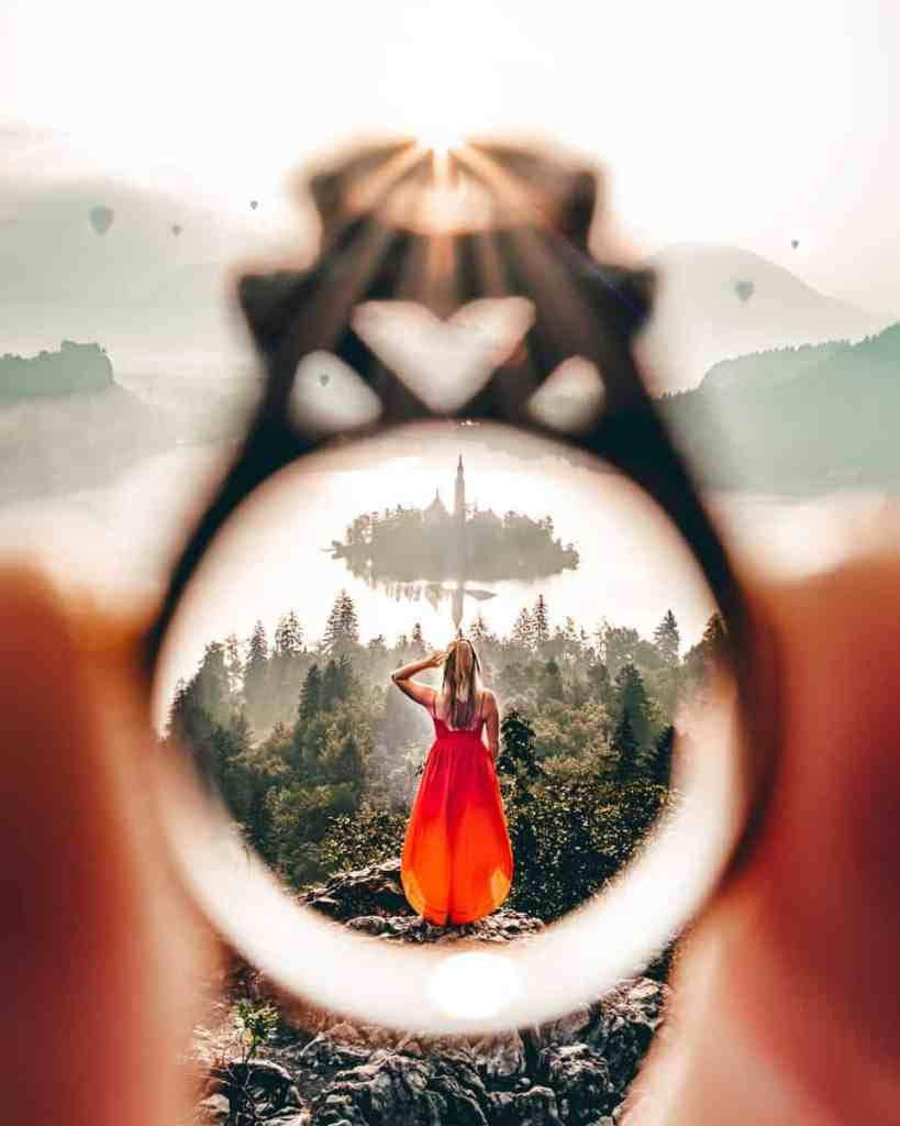 Girl in red dress overlooking Lake Bled framed through a wedding ring.