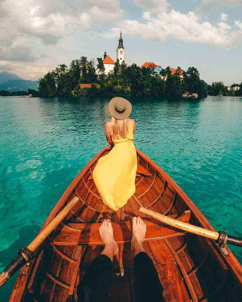 Girl in yellow dress in a row boat facing Bled Island