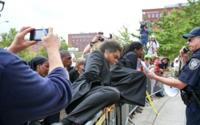Rev. Sekou, with Cornel West, climbing over police barricades in Ferguson