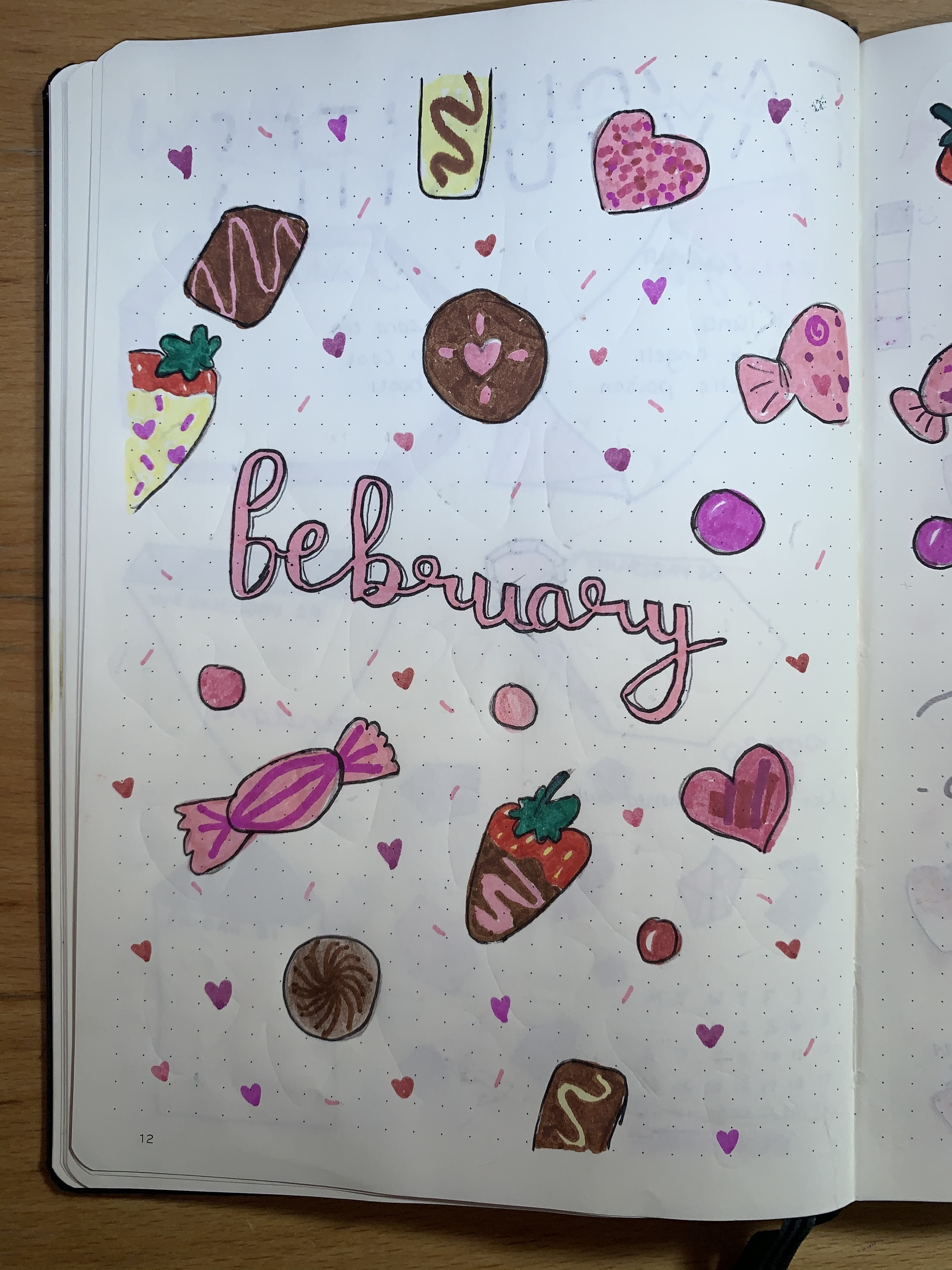 February bullet journal cover page decorated with chocolates and chocolate dipped strawberries