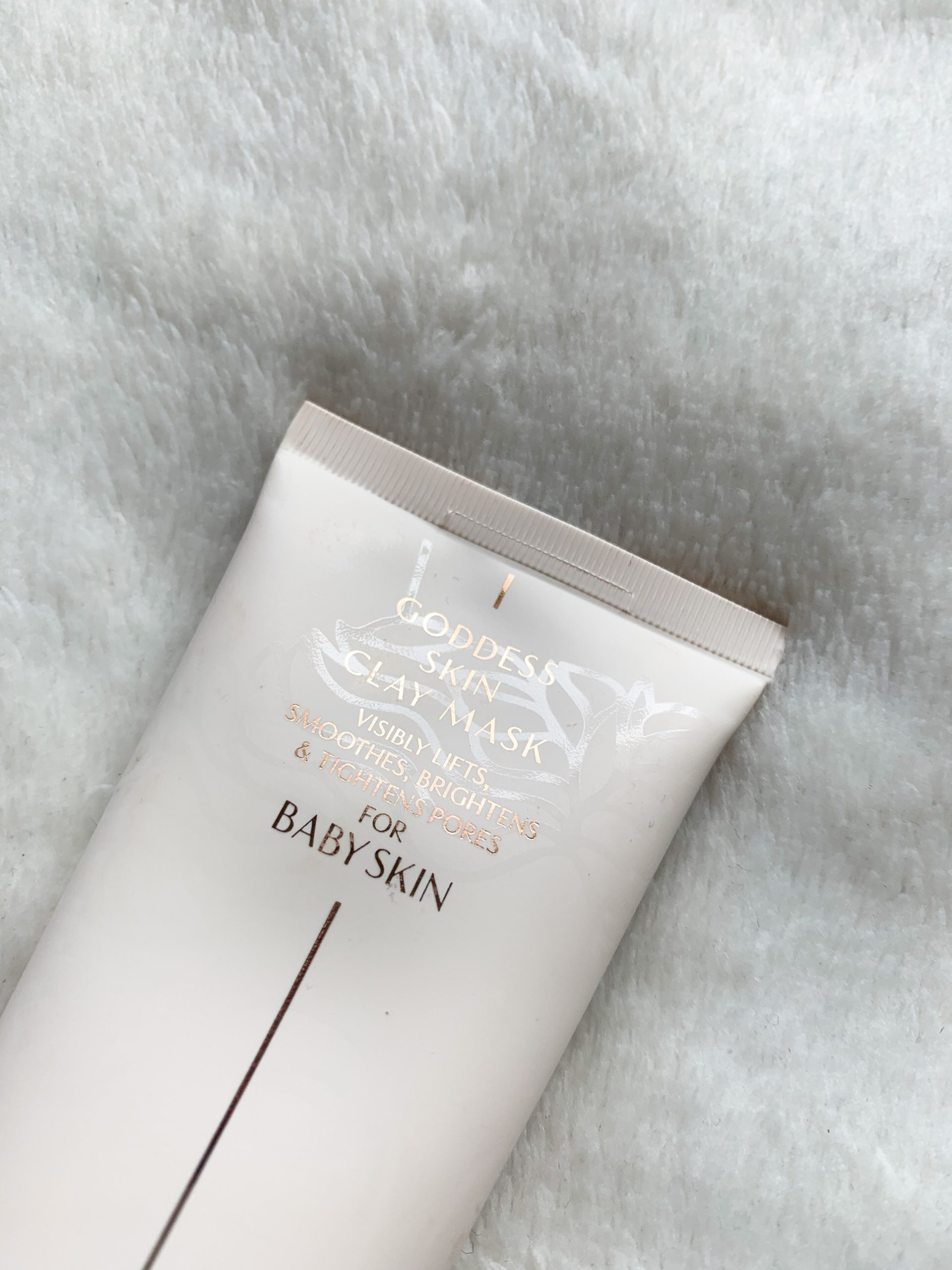 Charlotte Tilbury goddess skin clay mask against a white fluffy blanket
