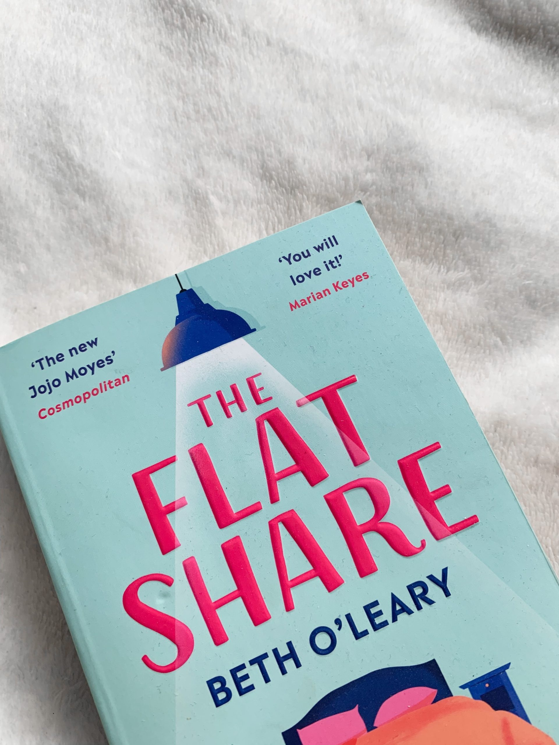 The Flat Share by Beth O'Leary on a white, soft blanket