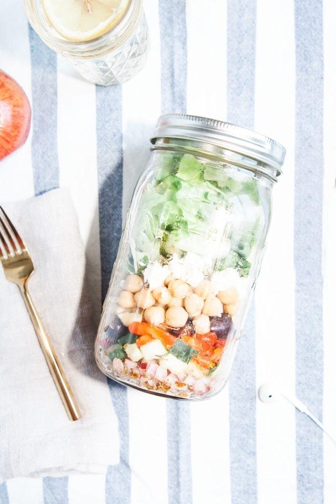 Chopped greek salad in a mason jar.