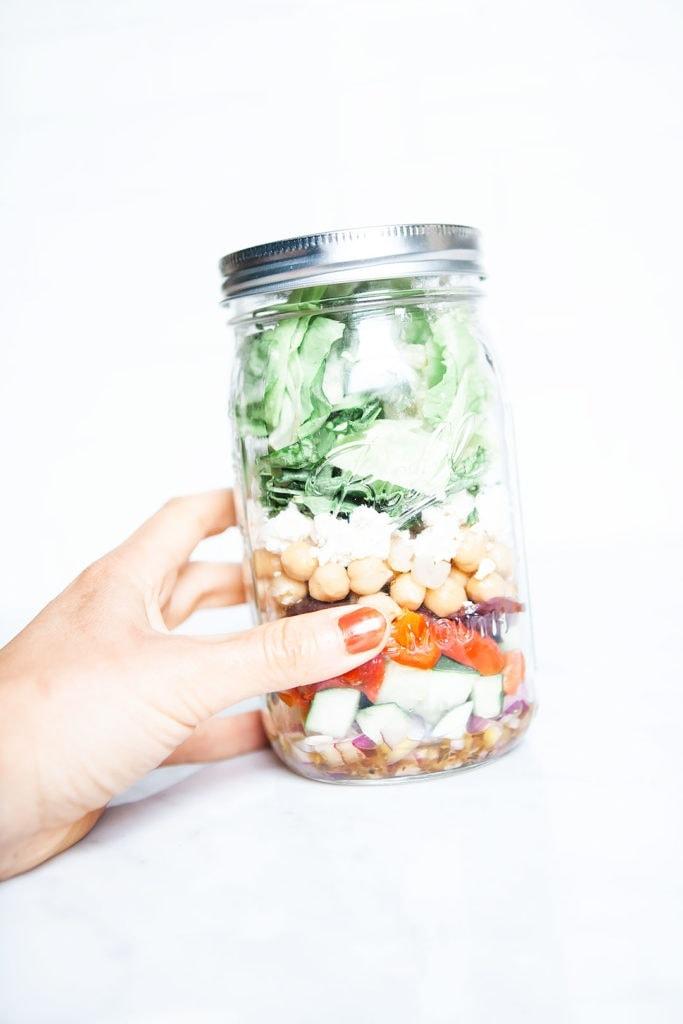 Chopped Greek salad being held in a mason jar.