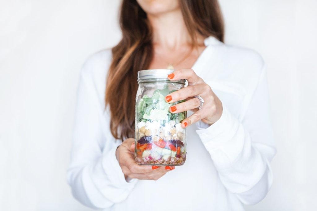 Woman holding layered salad in a mason jar.