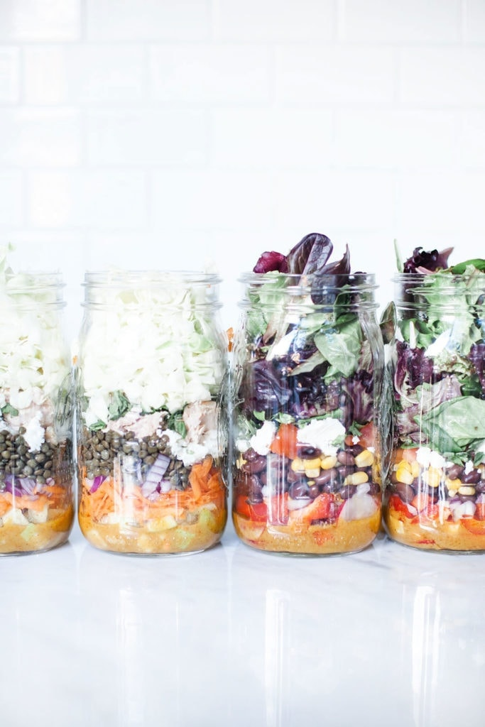 Layered salads in mason jars from the side.
