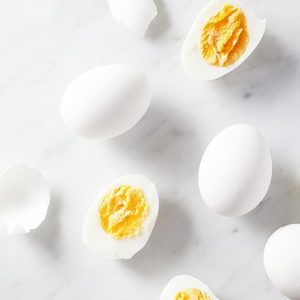 Hardboiled eggs on white marble surface.