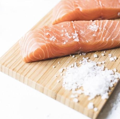 Raw salmon on cutting board.