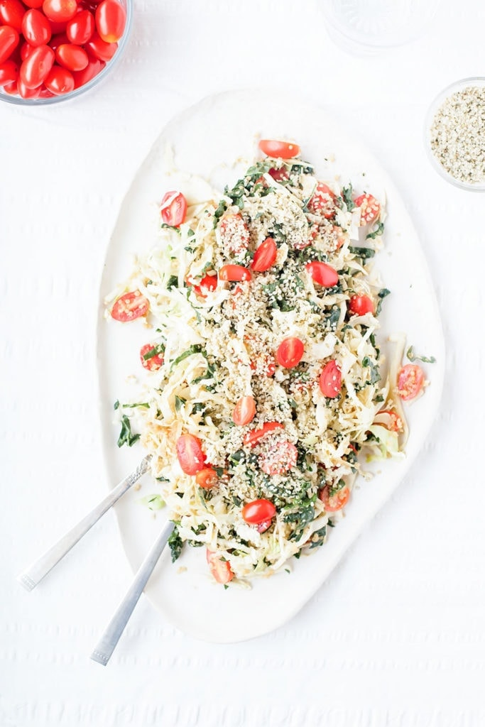 Kale and cabbage salad on a white platter.