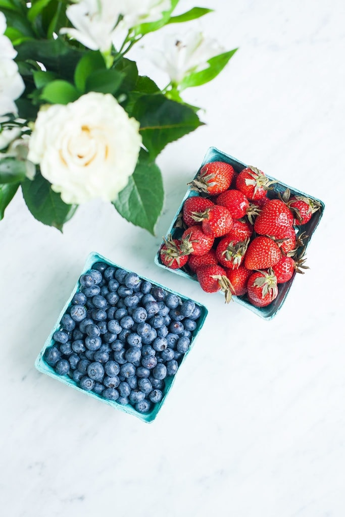 A container of blueberries and a container of strawberries from above with a vase of flowers.