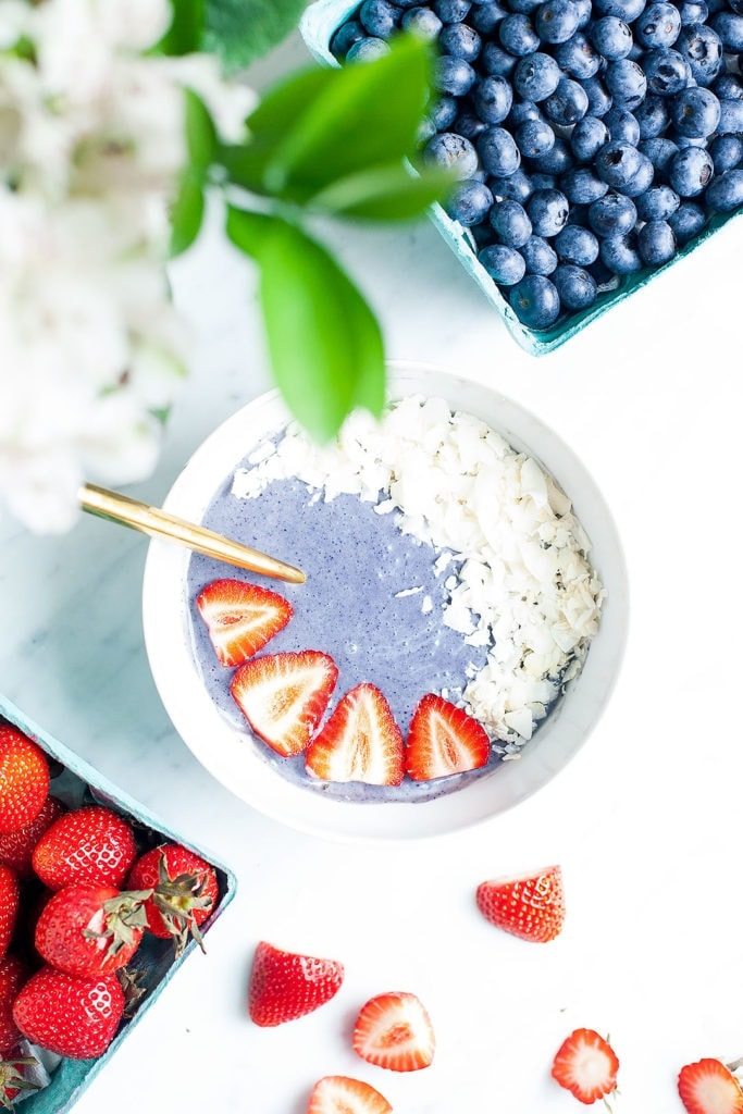 Blueberry smoothie bowl from above with strawberries in the corner.