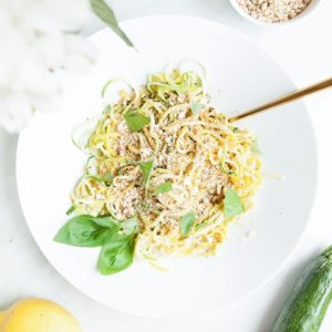 Lemony spiralized zucchini salad in a white dish from above.