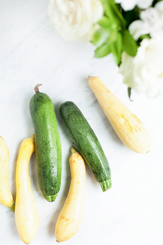 Green and yellow zucchini on a white background.