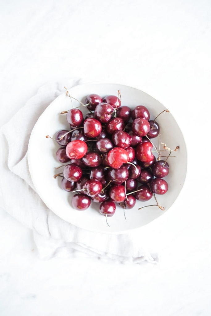 Cherries in a white bowl shot from overhead.
