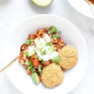 Chili in a white bowl with gluten-free cornbread.