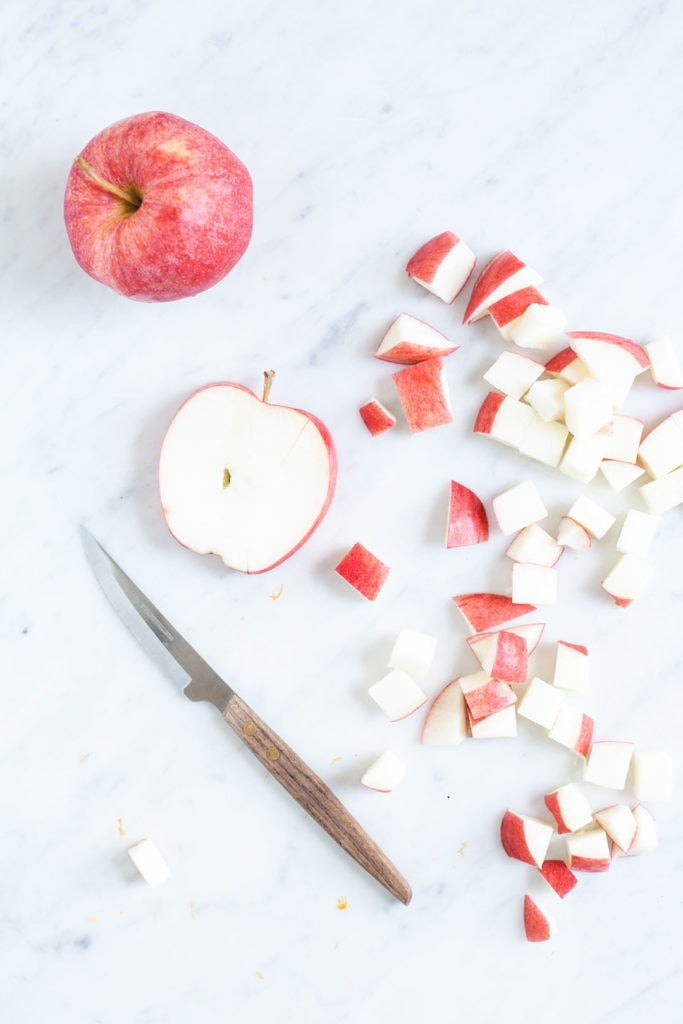 Apples chopped on a white marble background.