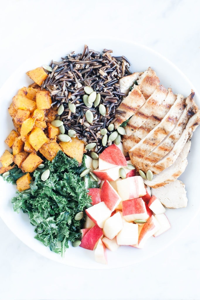 Fall harvest bowl with apples, squash, chicken, kale, and wild rice in a white bowl.
