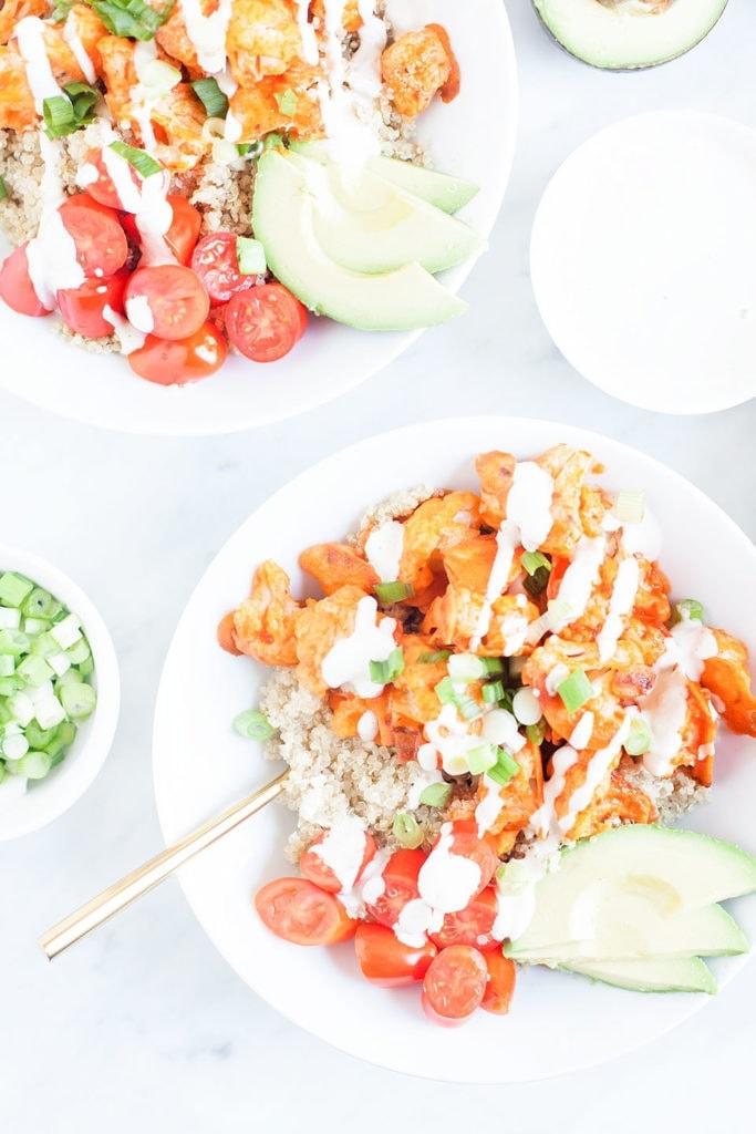 Buffalo cauliflower bowls with vegan ranch dressing in a white bowl.