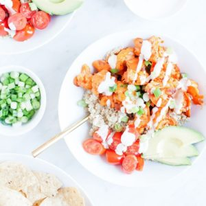 Buffalo cauliflower bowls with vegan ranch dressing in a white bowl.