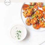 Gluten-free buffalo cauliflower wings on a white plate with cashew ranch.