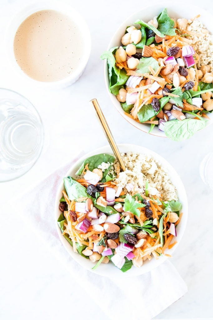 Moroccan chickpea salad in white bowls with a bowl of tahini dressing.
