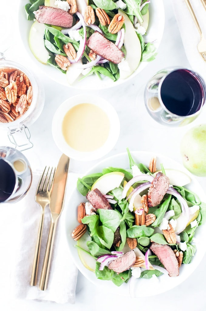 Steak, pear, and goat cheese salad in a white bowl with a small bowl of honey-mustard dressing and red wine.