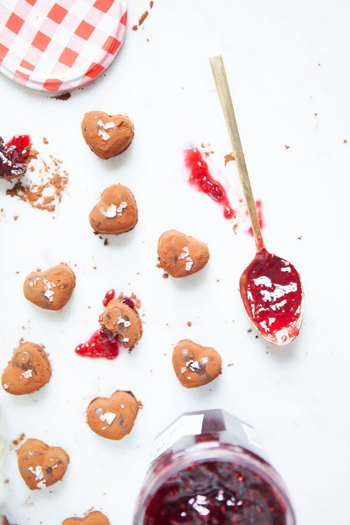 Vegan chocolate raspberry truffles with spoonful of jam on white background.