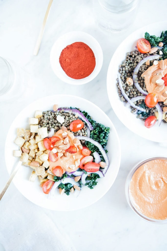 Lentil bowls with gluten-free romesco sauce in white bowls on white background.