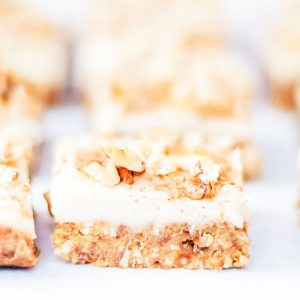 Carrot cake bars with vegan cream cheese frosting, photographed from the side.