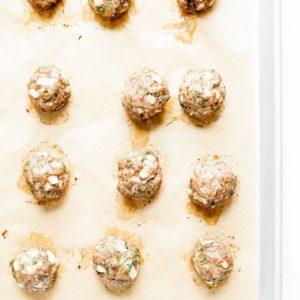 Turkey zucchini meatballs on a baking tray.