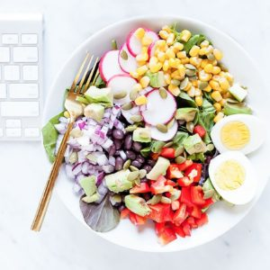 Colorful Southwestern salad in a white bowl on a desk with a computer keyboard.