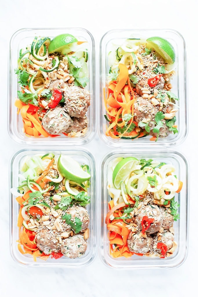 Spiralized salad in four meal prep containers.
