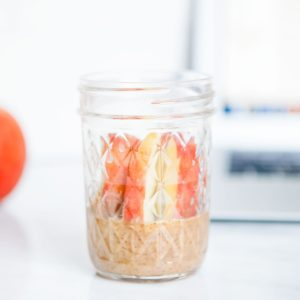 Sliced apples and almond butter in a mason jar.