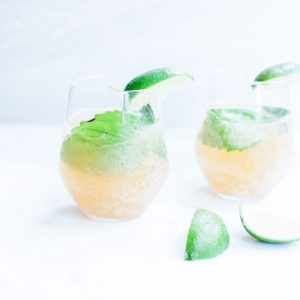 Two basil kombucha mojitos in glasses shot from the side with lime slices.